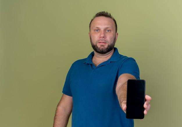 Erwachsener slawischer mann, der mobiltelefon ausdehnt