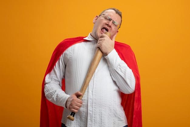 Erwachsener slawischer superheldenmann im roten umhang, der brille trägt, die mit geschlossenen augen singt, die baseballschläger als mikrofon verwendet, das auf orange wand mit kopienraum isoliert wird