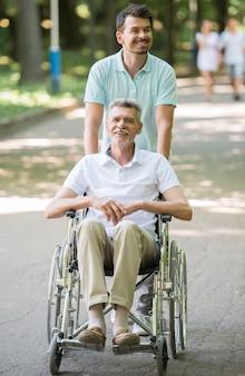 Erwachsener sohn, der mit behindertem vater im rollstuhl im freien geht