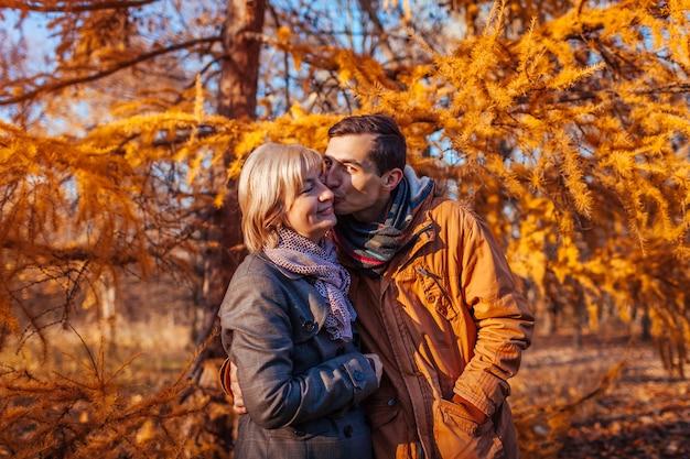 Erwachsener sohn, der seine mittlere gealterte mutter im herbstpark küsst