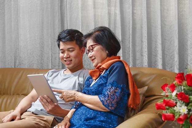 Erwachsener sohn und ältere mutter singen ein lied, während sie entspannt auf der couch sitzen
