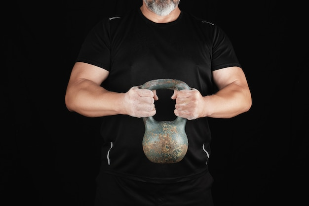 Erwachsener starker athlet in der schwarzen kleidung, die ein eisen kettlebell auf seinen ausgestreckten armen hält