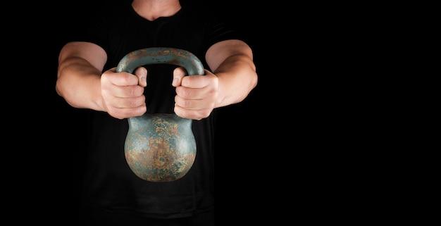 Erwachsener starker athlet in schwarzer kleidung, der eine eiserne kettlebell auf seinen ausgestreckten armen hält