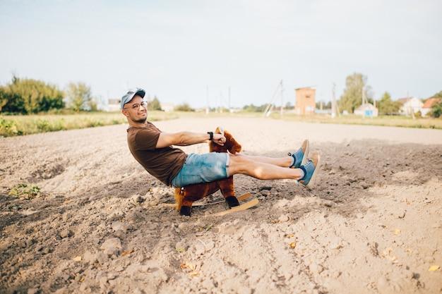 Erwachsener stilvoller mann, der spielzeugpferd auf feld im freien reitet. junge lustige ungewöhnliche seltsame männliche person mit lächelndem gesichtslebensstilporträt. glückliche junge kindheitserinnerungen.