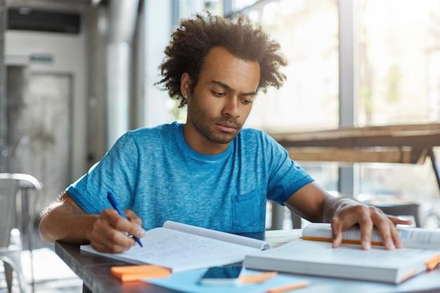 Erwachsener student, der drinnen in einem geräumigen raum sitzt, der feierlichen ausdruck sieht, der in bücher und notizbuch schaut, etwas schreibt, während er sich für klassen vorbereitet. studien- und lernkonzept