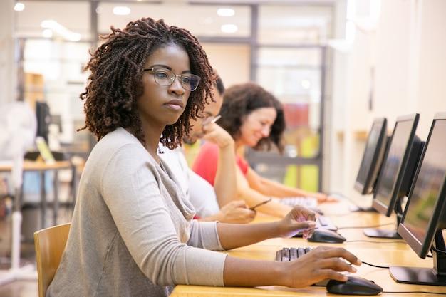 Erwachsener student der schwarzen frau, der in der computerklasse arbeitet