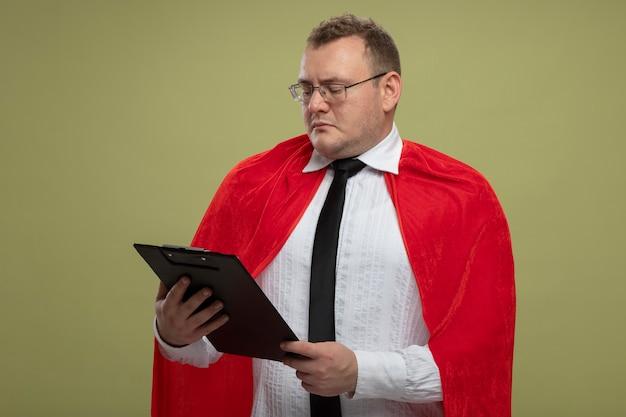 Erwachsener superheldenmann im roten umhang, der brillen hält und klemmbrett lokalisiert auf olivgrüner wand hält