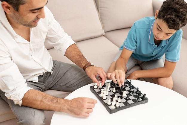 Erwachsener und kind des hohen winkels, die schach spielen