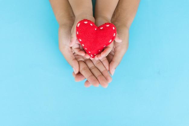 Erwachsener und kind, die rotes herz in den händen, in der liebe und im gesundheitswesenkonzept halten.