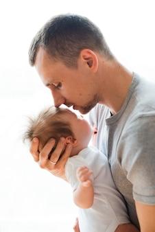 Erwachsener vater, der baby in der stirn küsst