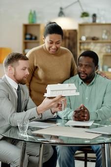 Erwachsenes afroamerikanisches paar, das besuch eines professionellen finanzbuchhalters hat, der beratung über haushypothek gibt