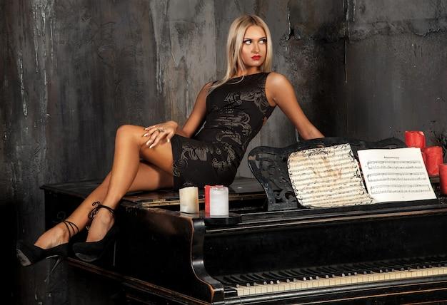 Erwachsenes blondes mädchen, das auf klavier liegt und wegschaut