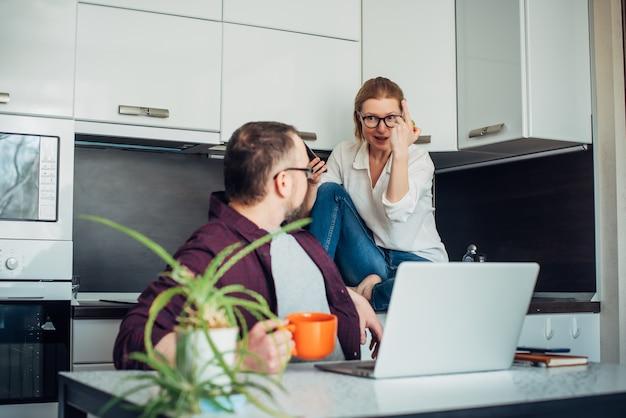 Erwachsenes ehepaar in der hauptküche. mann sitzt mit laptop am tisch und blickt auf seine frau zurück. frau mit brille macht handgesten. gemeinsame familienfreizeit und arbeit während des lockdowns.