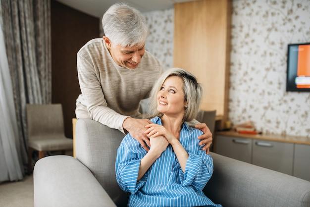 Erwachsenes liebespaar, mann umarmt frau zu hause. reifer ehemann und ehefrau sitzen auf der couch und pflegende, glückliche familie