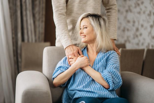 Erwachsenes liebespaar, mann umarmt frau zu hause