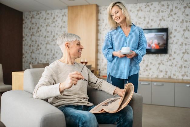Erwachsenes liebespaar zu hause am morgen, frau, die sich um mann kümmert. reifer ehemann mit zeitung im stuhl sitzend, frau bringt kaffee, glückliche familie
