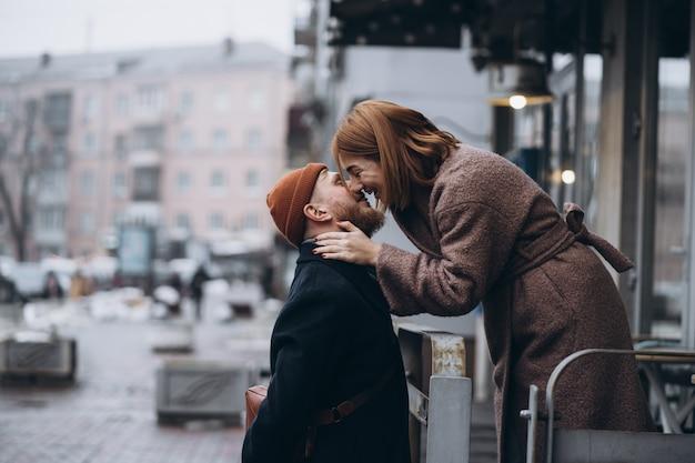 Erwachsenes liebevolles paar, das auf einer straße küsst