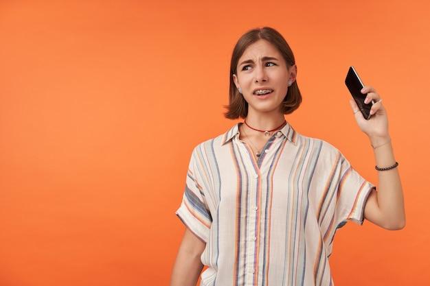 Erwachsenes mädchen, das unglücklich schaut und ein telefon auflegt. im gegensatz zu anruf. der schüler nimmt ein telefon in die hand und trägt ein gestreiftes hemd, zahnspangen und armbänder. beobachten sie links den kopierbereich über der orangefarbenen wand