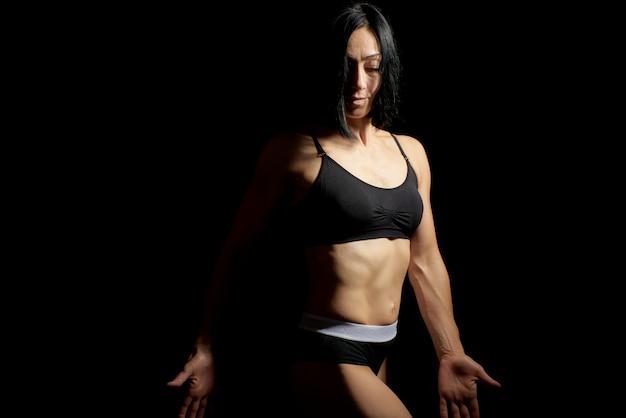 Erwachsenes mädchen mit einem sport stellt im schwarzen bh und in schwarzen kurzen hosen dar, die auf einem dunklen hintergrund, muskulöser körper, schwarzes haar stehen