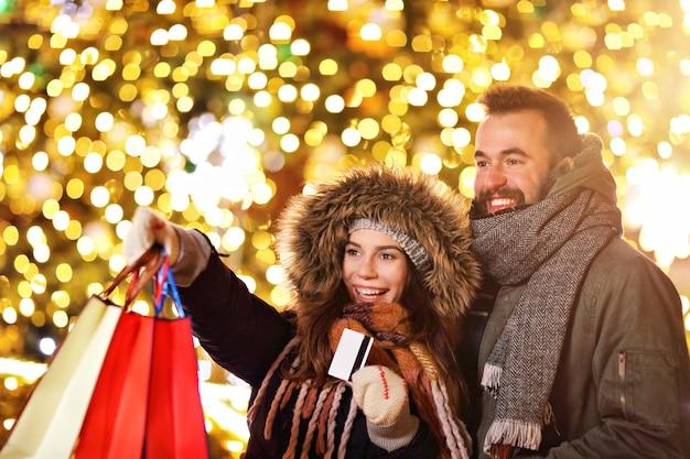 Erwachsenes paar beim einkaufen in der stadt während der weihnachtszeit