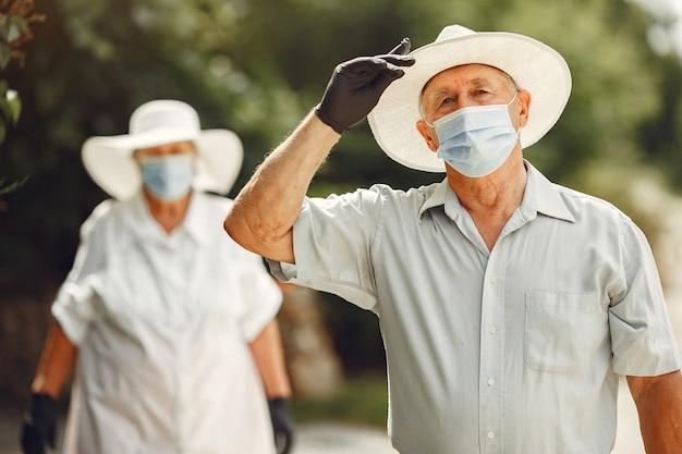 Erwachsenes paar in einem sommergarten. coromavirus-thema. menschen in einer medizinischen maske. hübscher senior in einem weißen hemd.