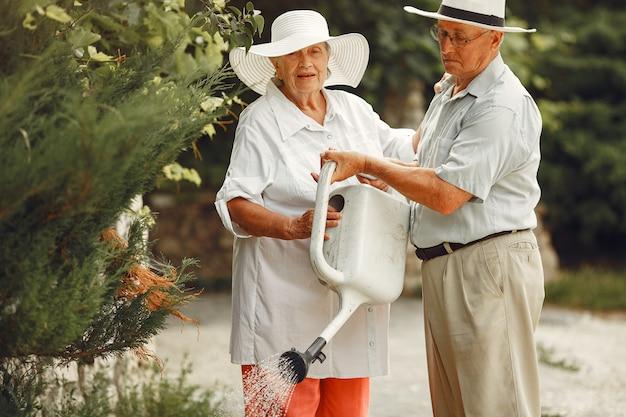 Erwachsenes paar in einem sommergarten. hübscher senior in einem weißen hemd. frau mit hut. familienbewässerung.