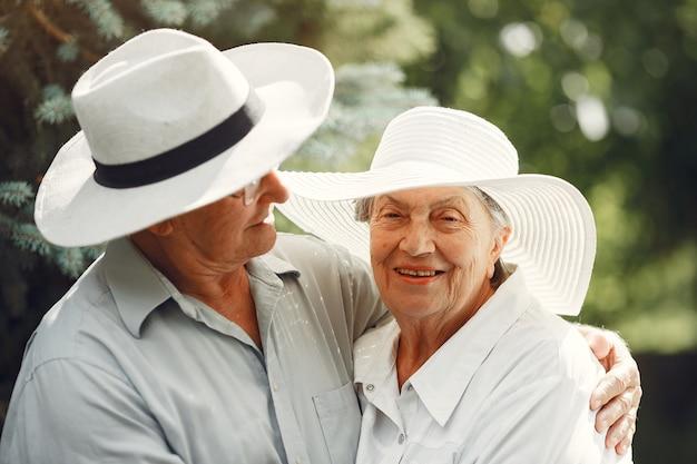 Erwachsenes paar in einem sommergarten. hübscher senior in einem weißen hemd. frau mit hut.