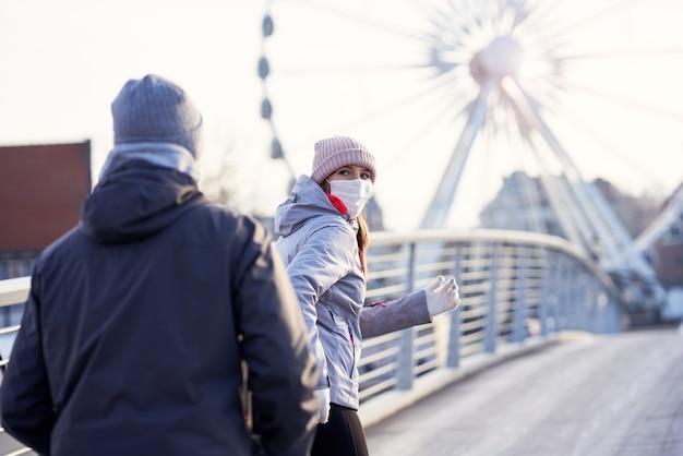 Erwachsenes paar joggen in der stadt in masken während der sperrpandemie