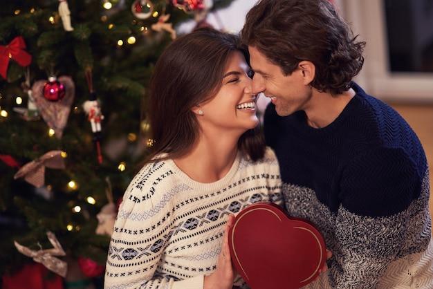 Erwachsenes paar mit geschenk über weihnachtsbaum