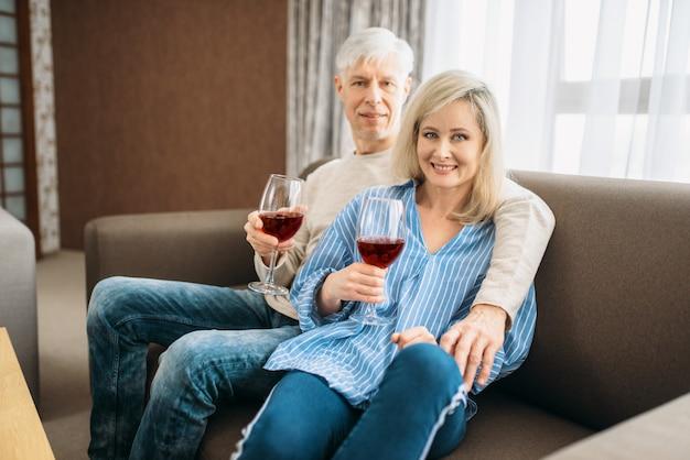 Erwachsenes paar sitzt auf der couch und trinkt wein