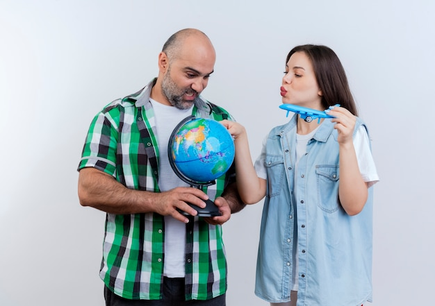 Erwachsenes reisendes paar beeindruckte mann, der globus und frau hält modellflugzeug, das globus berührt und beide globus betrachtet
