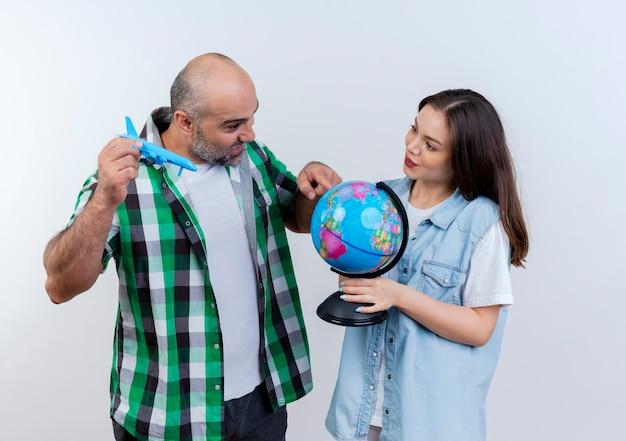 Erwachsenes reisendes paar beeindruckte mann, der modellflugzeug hält, das globus betrachtet und berührt und erfreute frau, die globus hält und ihn ansieht