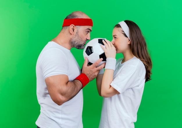 Erwachsenes sportliches paar, das stirnband und armbänder trägt, fußball hält und küsst und einander ansieht