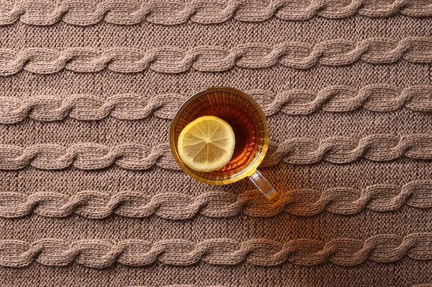 Erwärmender herbsttee mit zitrone auf gemütlichem braunem pullover als hintergrund. sicht von oben.