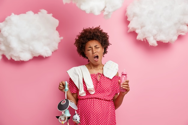 Erwartete mutter schwangere frau gähnt und fühlt sich müde, packt baby sachen in entbindungsheim, posiert mit windel, flasche, handy, steht drinnen über rosiger wand. schwangerschafts- und müdigkeitskonzept