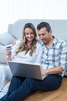 Erwartung der paare, die auf sofa sitzen und laptop verwenden