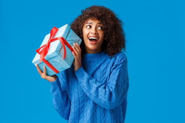 Erwartungen, urlaub und winterkonzept. aufgeregte fröhliche afroamerikanische frau, die box mit geschenk schüttelt, wollen geschenk auspacken sehen, was drinnen neugierig und amüsiert steht, verträumt lächelnd