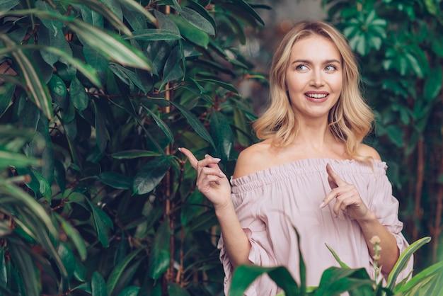 Erwogene blonde junge frau, die nahe den grünpflanzen steht, die ihren finger zeigen