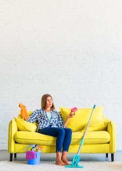 Erwogene junge frau, die auf dem gelben sofa hält schwamm- und gummihandschuhe sitzt