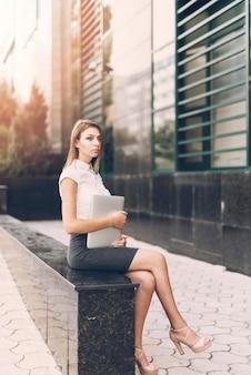Erwogene junge geschäftsfrau, welche die digitale tablette sitzt auf marmorbank hält