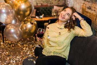 Erwogene lächelnde Frau in der Partei, die das Weinglas sitzt auf Couch hält
