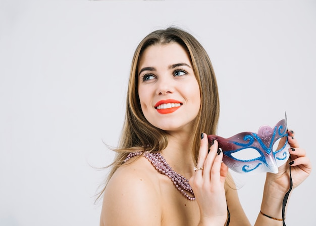 Erwogene lächelnde frau mit der perlenhalskette, die maskeradekarnevalsmaske hält