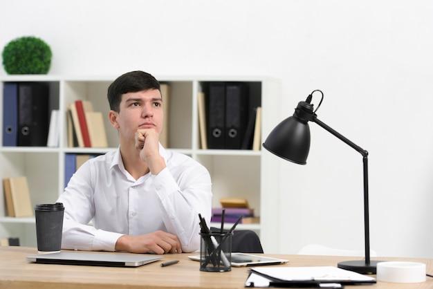 Erwogener junger geschäftsmann, der am arbeitsplatz im büro sitzt