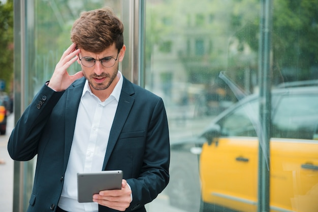 Erwogener junger geschäftsmann, der digitale tablette betrachtet