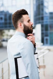Erwogener junger geschäftsmann mit dem klemmbrett, das seinen bart berührt