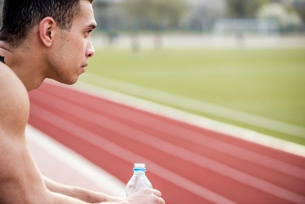 Erwogener junger männlicher athlet, der am stadion hält wasserflasche sitzt