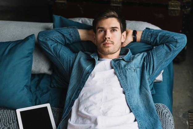 Erwogener junger mann, der auf dem bett oben schaut mit digitaler tablette liegt