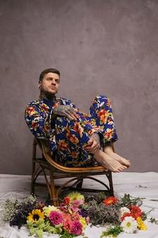 Erwogener junger mann, der auf stuhl mit den bunten blumen geworfen auf boden sitzt