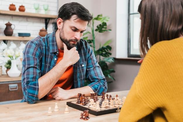 Erwogener junger mann, der zu hause das schachspiel mit ihrer frau spielt