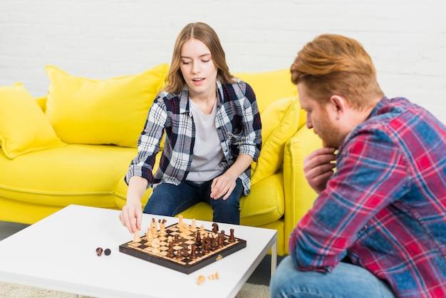 Erwogener mann, der ihre freundin zu hause spielt schach betrachtet